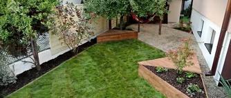 Jak ciekawie zaaranżować przestrzeń w ogrodzie? Donica z ławką, ścieżka z dębu, drewniane ogrodzenie